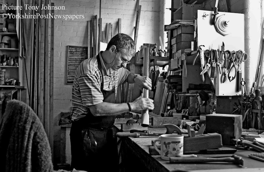 Black and white photograph of Terry Shires making an organ pipe.